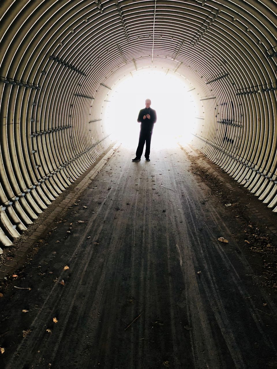 Full Length Of Man Standing In Tunnel