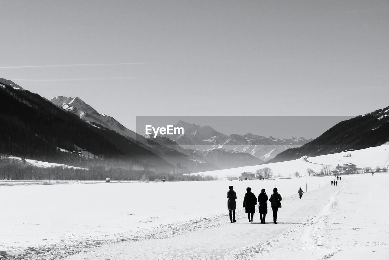 Rear view of friends walking on snow covered field by mountains against clear sky