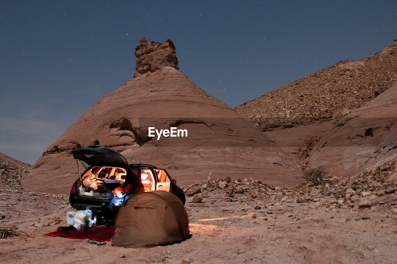 Man Resting By Tent At Desert