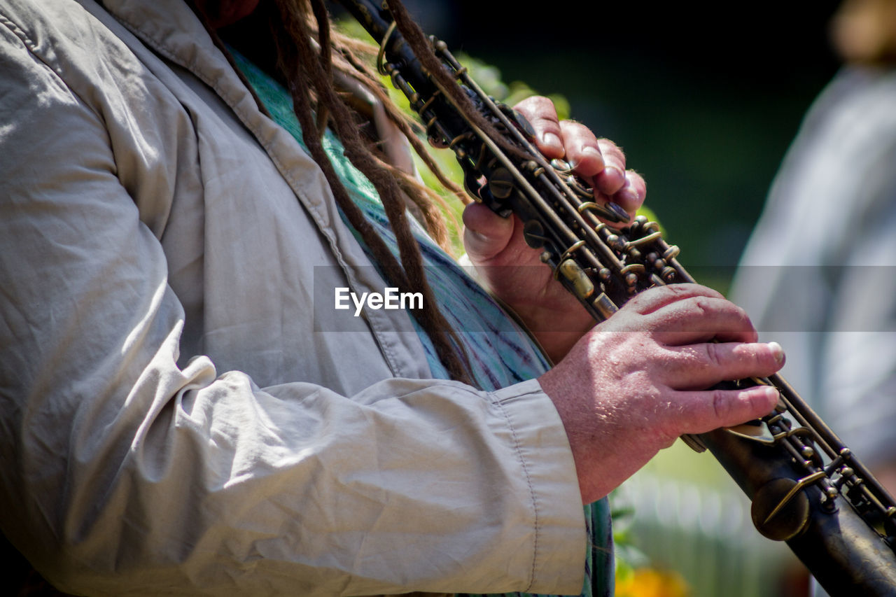 Midsection Of Street Musician Playing Oboe