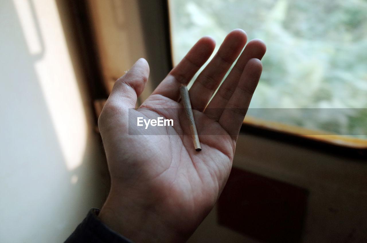 Close-Up Of Human Hand With Marijuana Joint