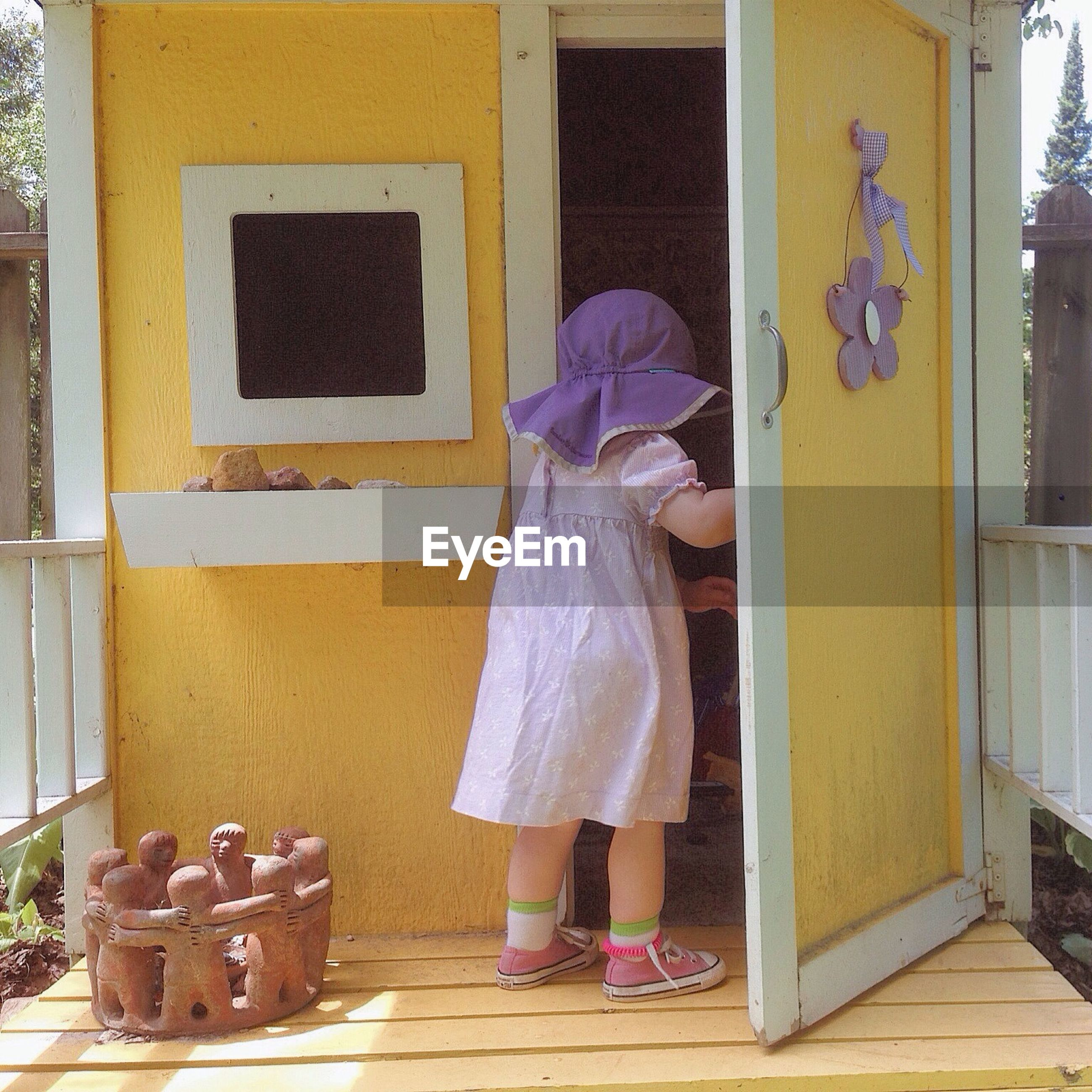 Rear view of girl standing at doorway