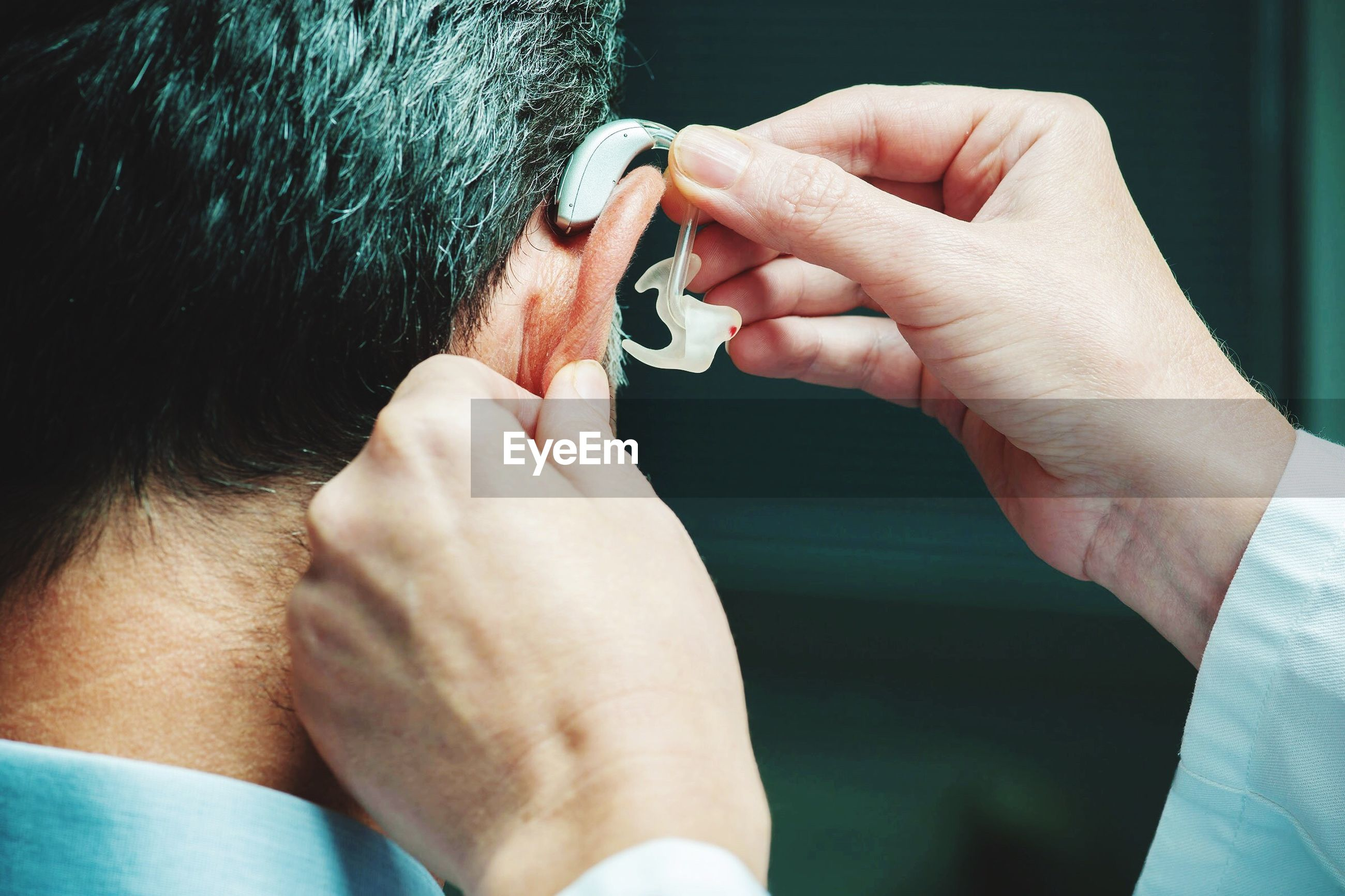 Cropped hand of person adjusting man hearing aid