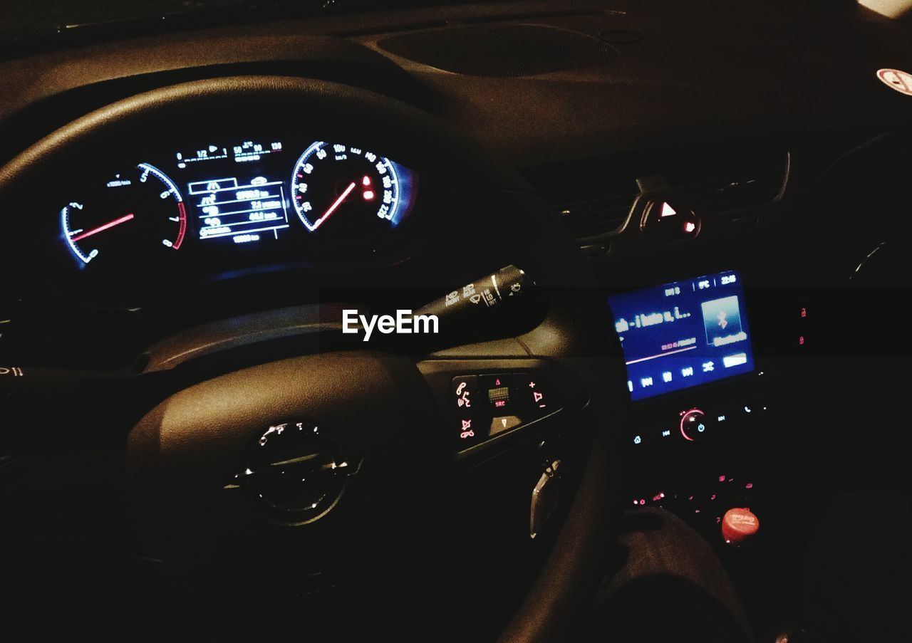 vehicle interior, car interior, transportation, dashboard, car, speedometer, mode of transport, land vehicle, steering wheel, human hand, control, speed, journey, driving, technology, travel, human body part, gauge, close-up, control panel, illuminated, indoors, cockpit, one person, day, people