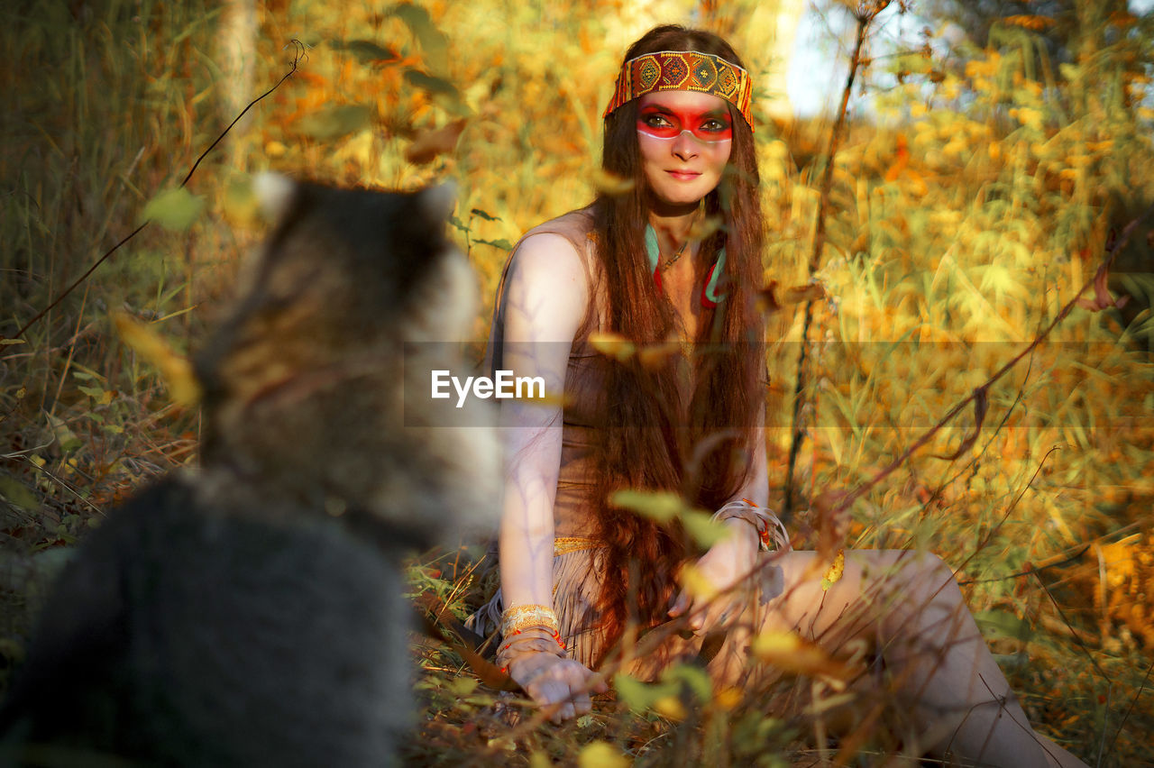 Young Woman Looking At Raccoon While Sitting In Forest