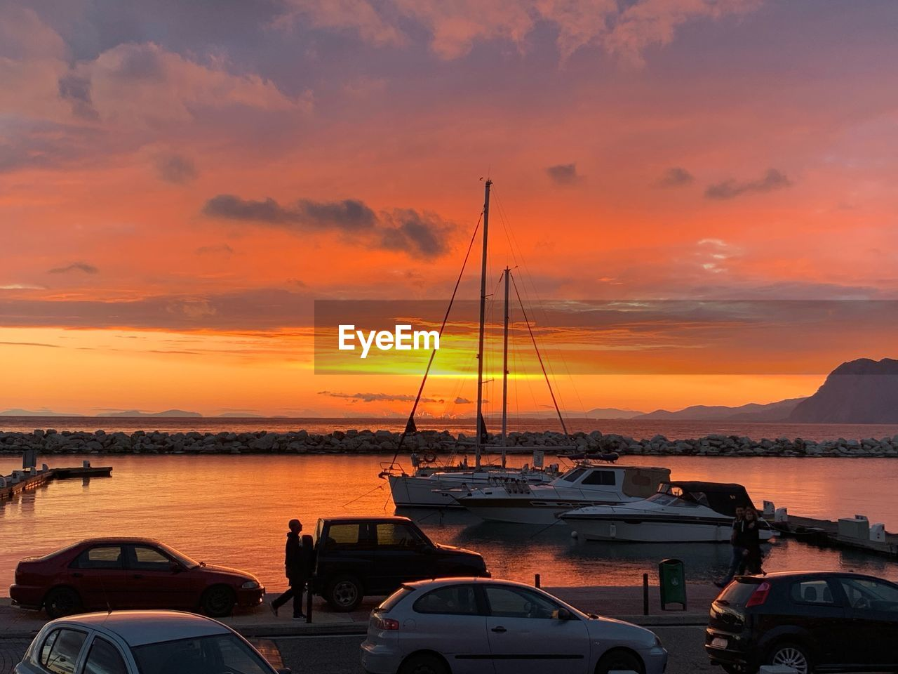 transportation, mode of transportation, sunset, water, sky, nautical vessel, moored, sea, cloud - sky, orange color, beauty in nature, sailboat, mast, scenics - nature, harbor, nature, pole, no people, tranquility, outdoors, yacht, marina, port