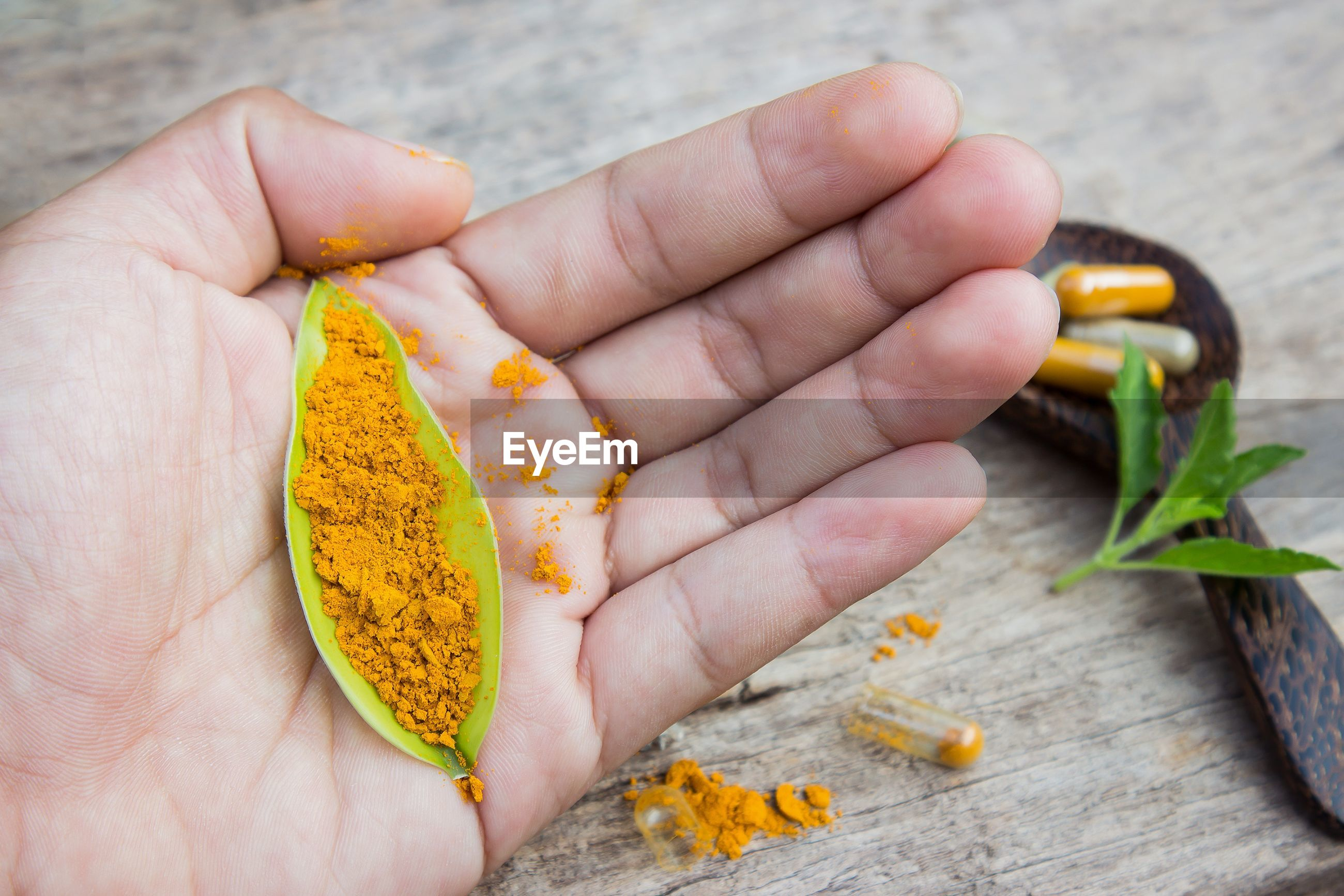 High angle view of turmeric in leaf on palm of hand