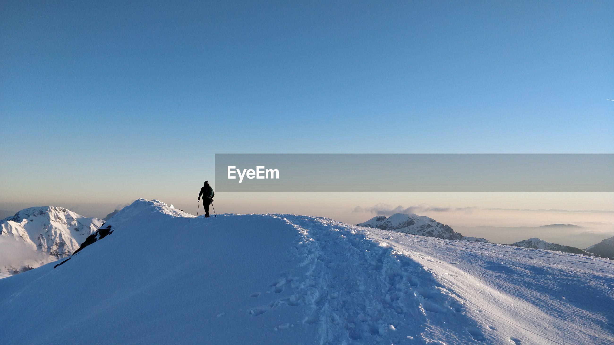 Man on snowcapped mountain against clear sky