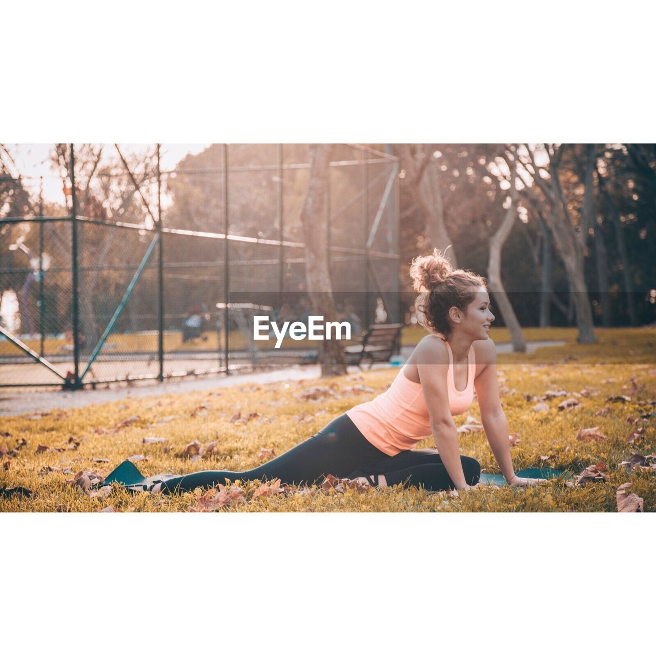 full length, lifestyles, exercising, real people, one person, day, leisure activity, sports clothing, outdoors, healthy lifestyle, balance, young women, young adult, smiling, tree, grass, only women, adult, people, adults only