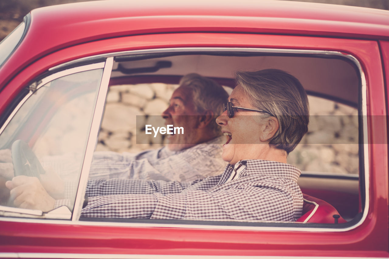 Side view of senior couple sitting in car