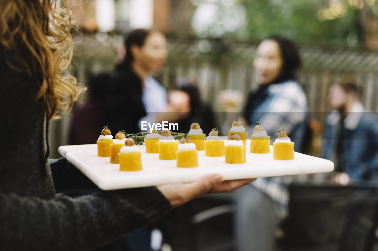 CLOSE-UP OF PEOPLE HOLDING CANDLES ON YELLOW OUTDOORS