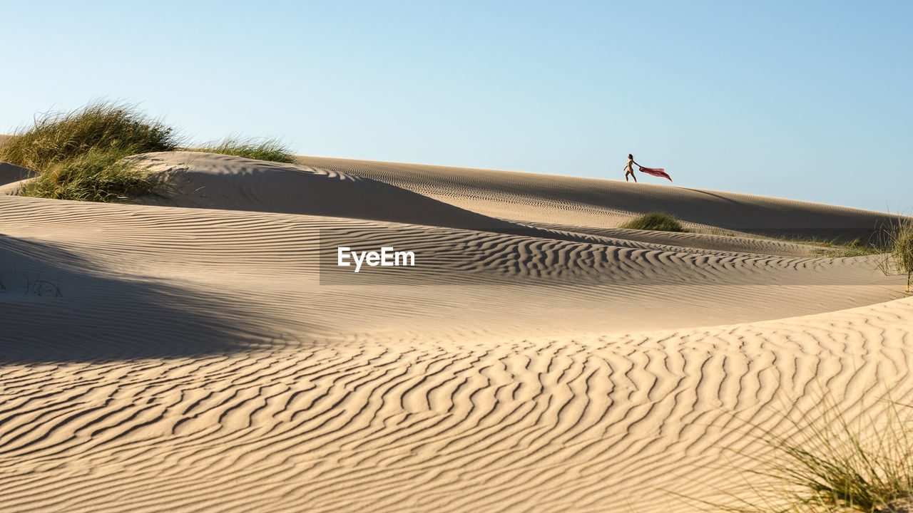 sand, sand dune, beach, desert, arid climate, nature, clear sky, scenics, day, outdoors, tranquil scene, landscape, travel destinations, tourism, tranquility, sunlight, beauty in nature, marram grass, sky, vacations, one person, people