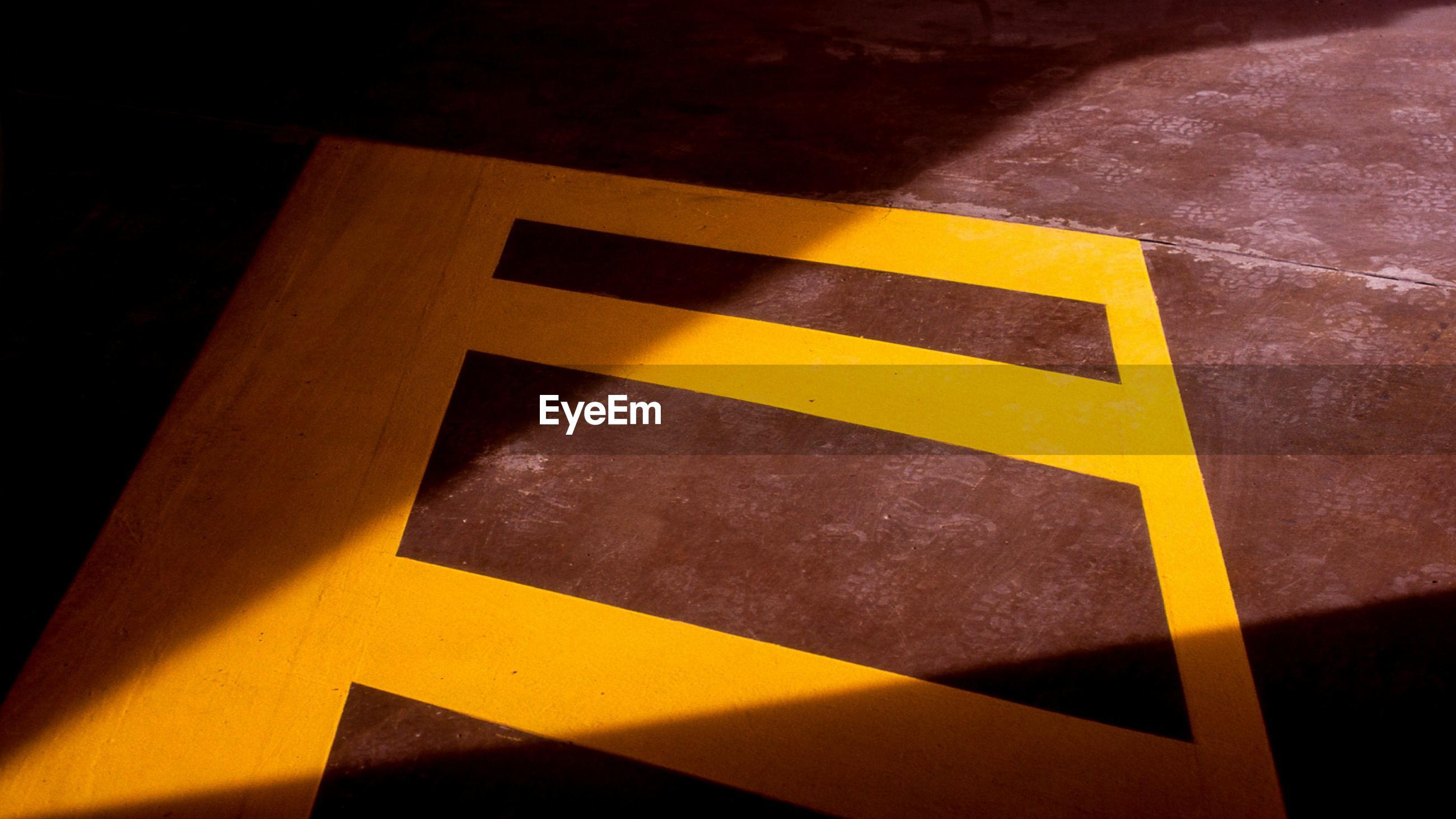High angle view of yellow marking in parking lot