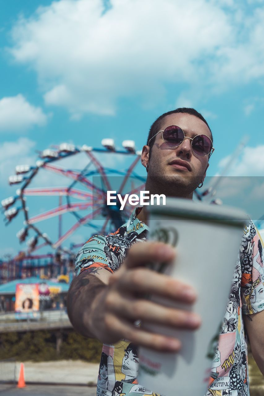 Portrait Of Young Man Wearing Sunglasses Holding Coffee While Standing Against Amusement Park