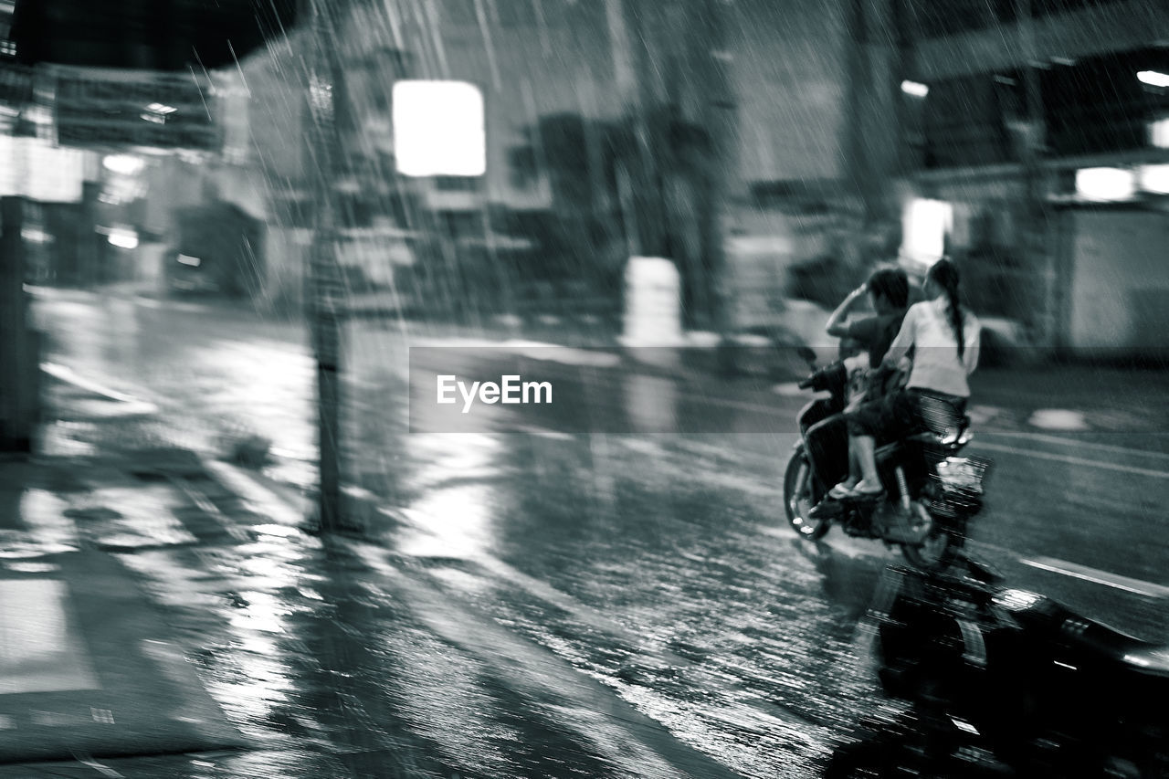 rain, weather, motorcycle, blurred motion, rainy season, motion, wet, speed, mode of transport, transportation, real people, riding, outdoors, land vehicle, day, building exterior, water, built structure, raindrop, men, architecture, road, city, lifestyles, illuminated, one person, biker, people