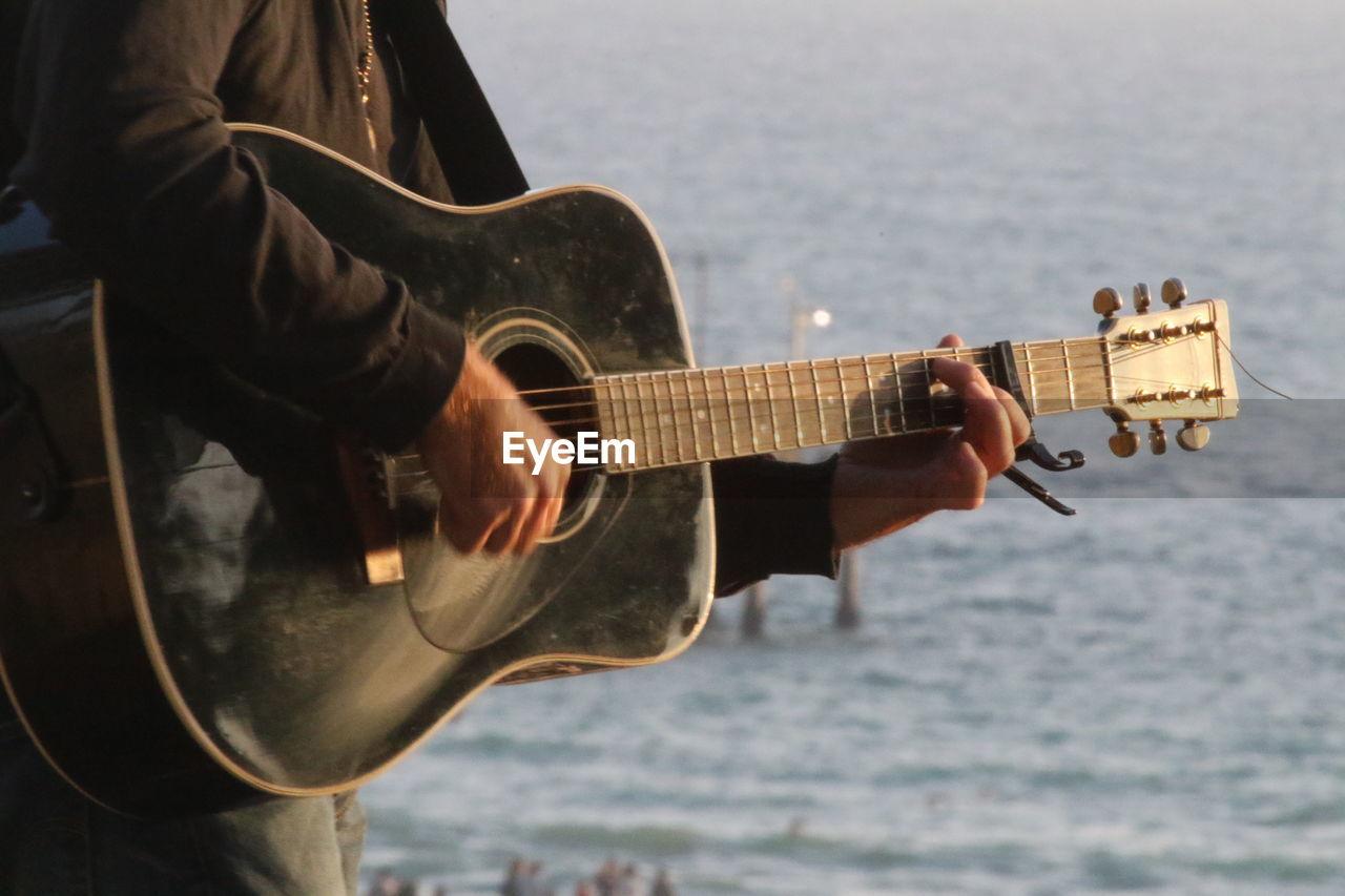 Close-up of man playing guitar at beach