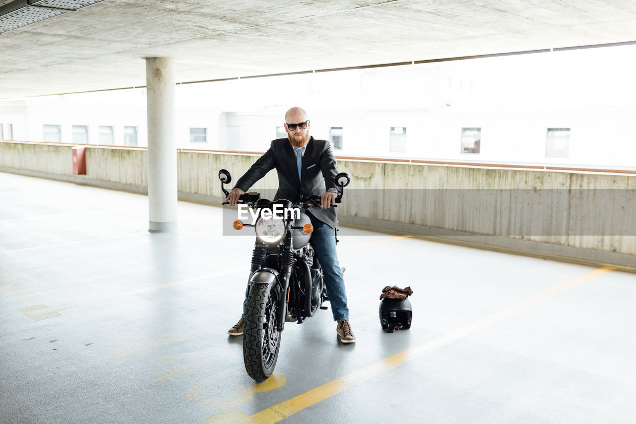 Man Sitting On Motorcycle In Building