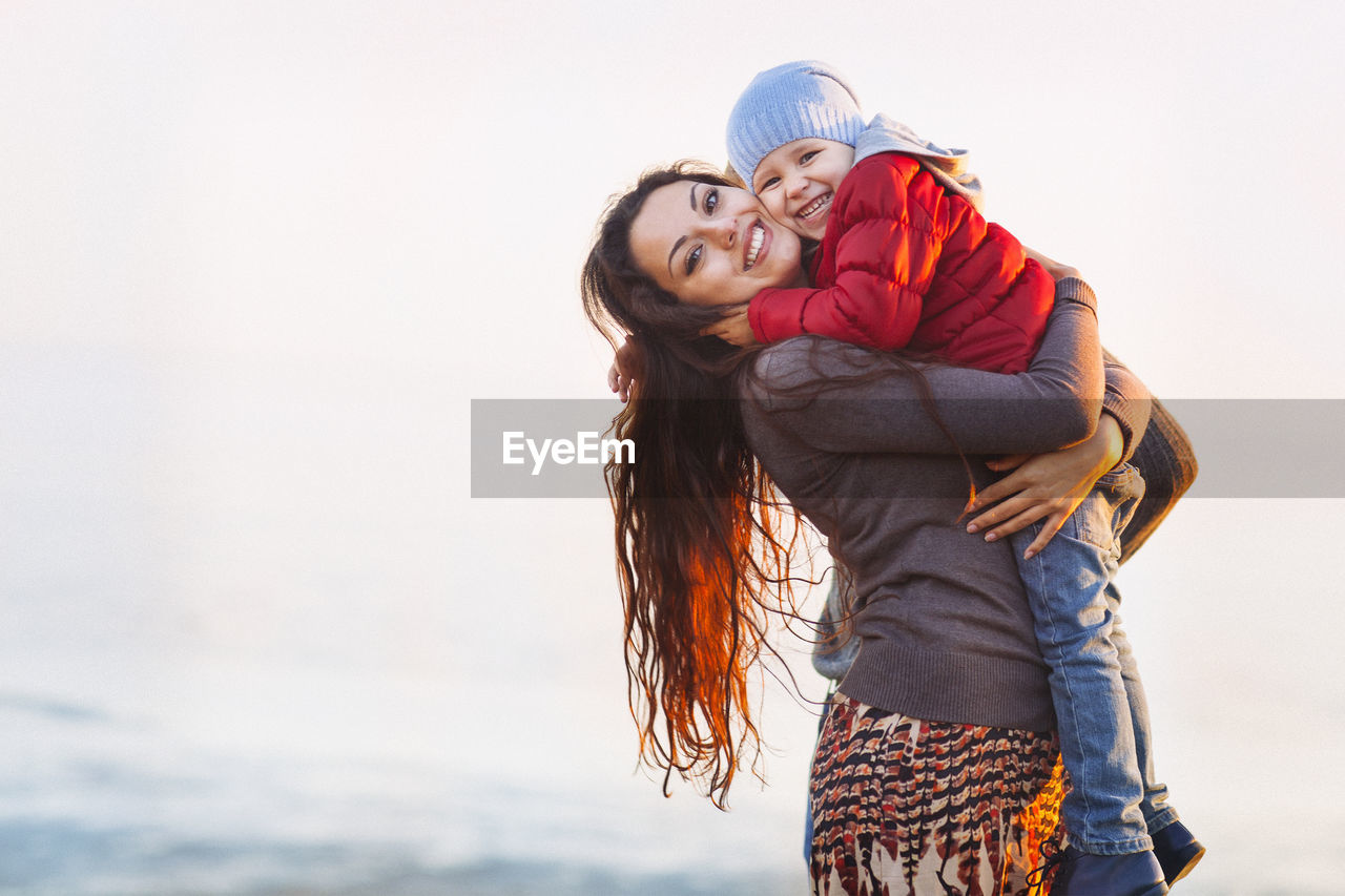 Mother holding daughter in arms against clear sky