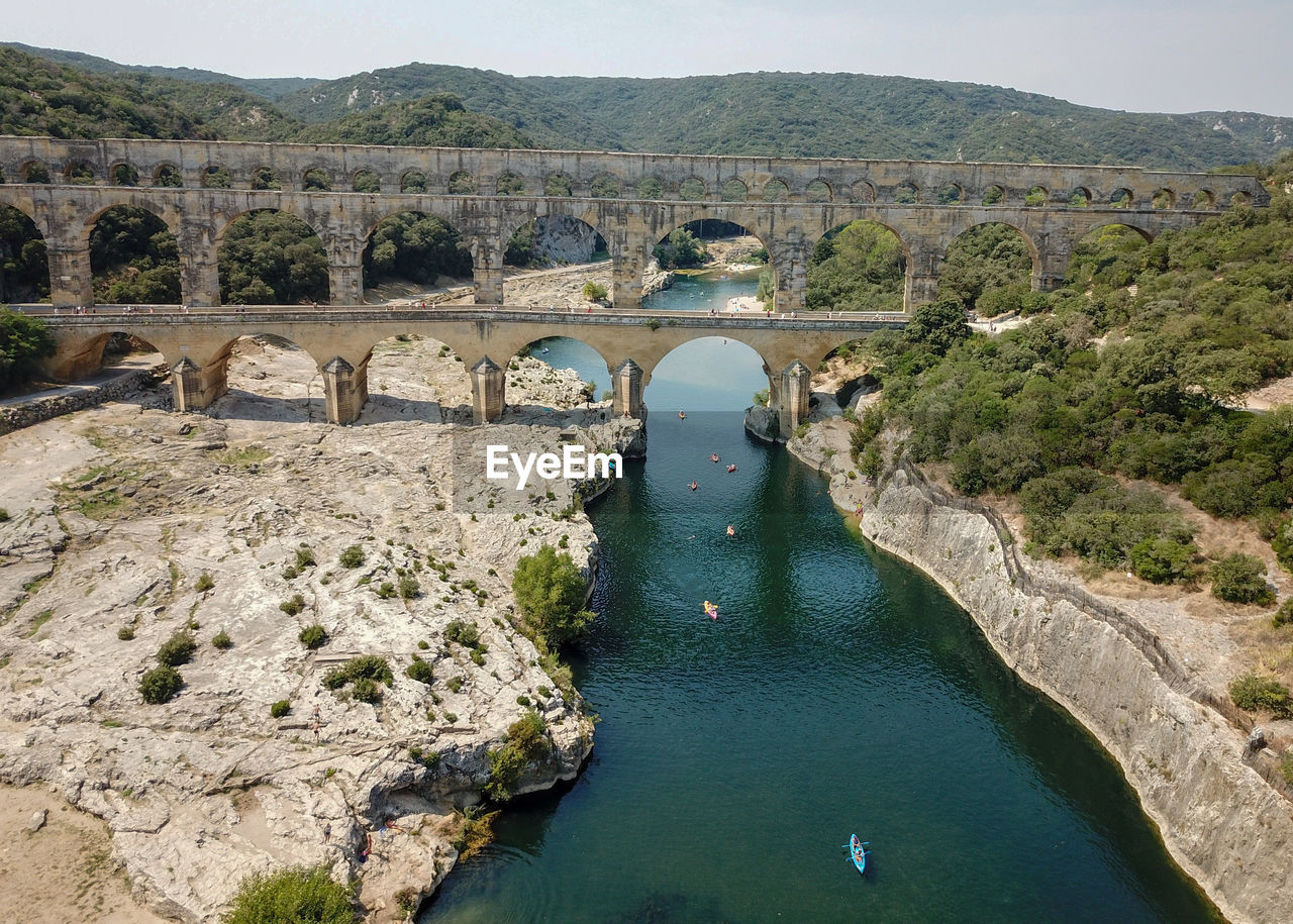 water, architecture, built structure, nature, bridge, day, mountain, river, scenics - nature, no people, connection, plant, bridge - man made structure, transportation, tranquility, tranquil scene, arch, beauty in nature, history, outdoors, arch bridge, ancient civilization