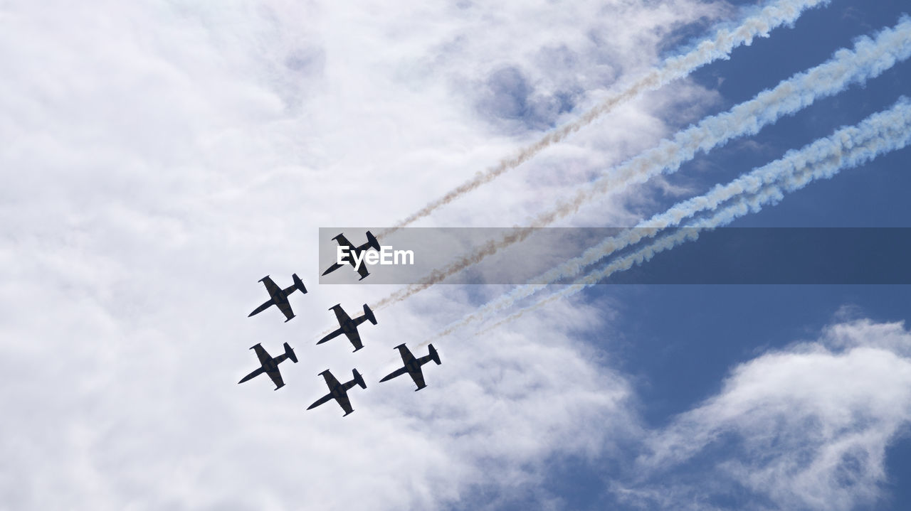 cloud - sky, airplane, air vehicle, flying, low angle view, sky, on the move, mode of transportation, vapor trail, transportation, airshow, motion, fighter plane, day, no people, speed, plane, cooperation, teamwork, smoke - physical structure, outdoors, aerospace industry