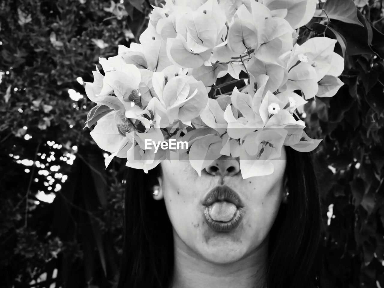 Close-Up Of Woman Sticking Out Tongue Behind Flowers