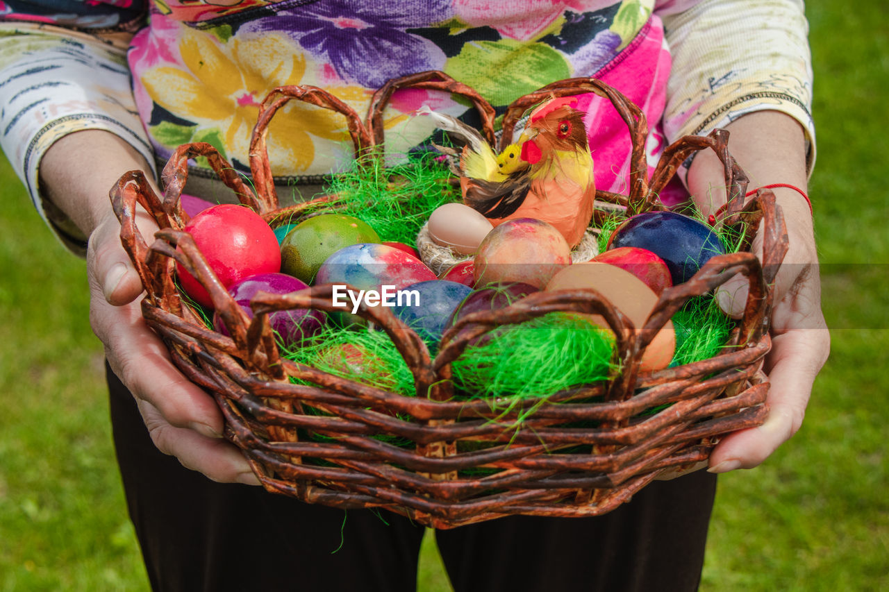 LOW SECTION OF WOMAN HOLDING COLORFUL BASKET
