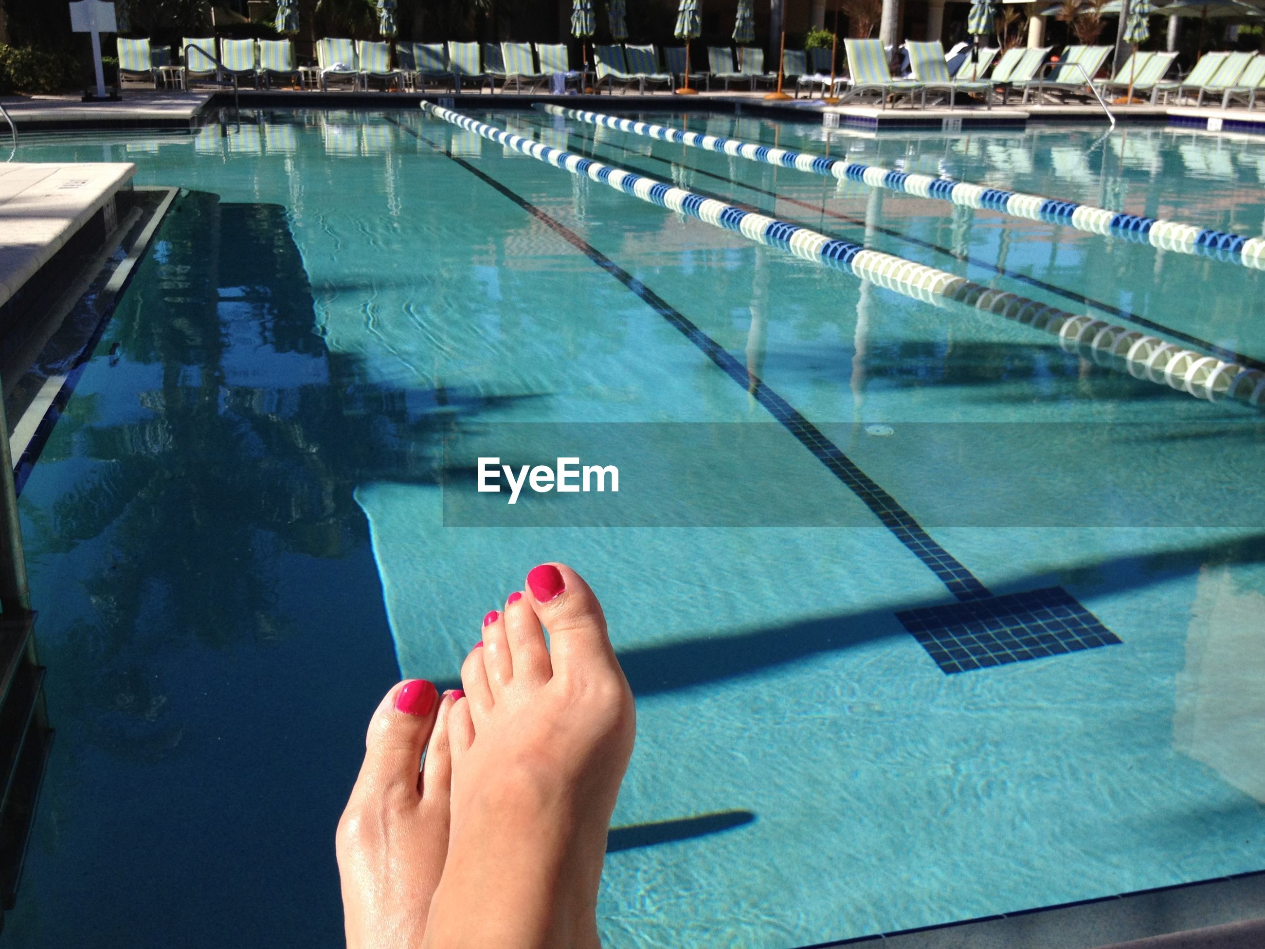 Low section of woman by swimming pool