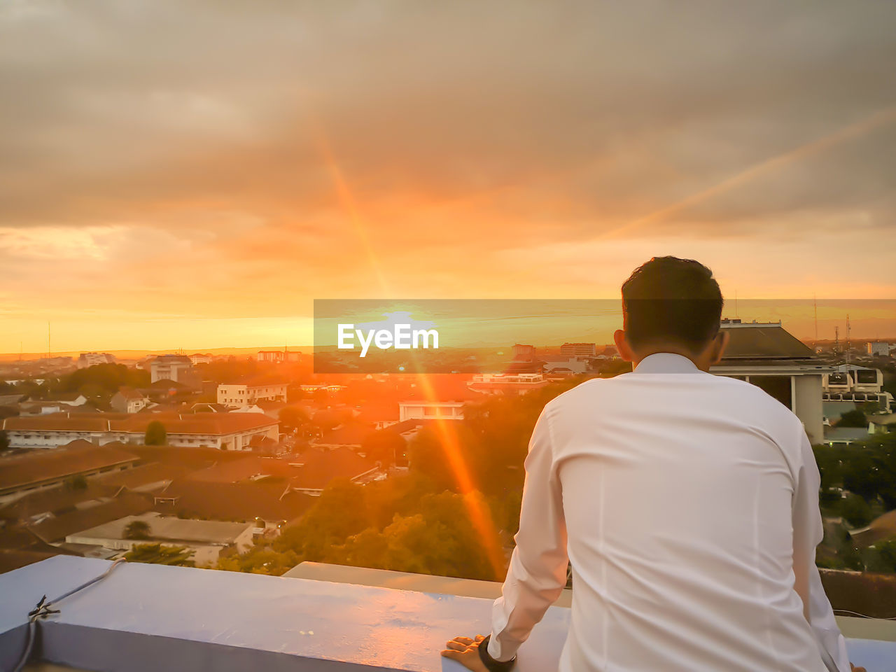 sunset, sky, rear view, architecture, one person, building exterior, built structure, cloud - sky, men, standing, orange color, real people, nature, city, lifestyles, leisure activity, sunlight, cityscape, sun, waist up, outdoors, lens flare, looking at view, contemplation