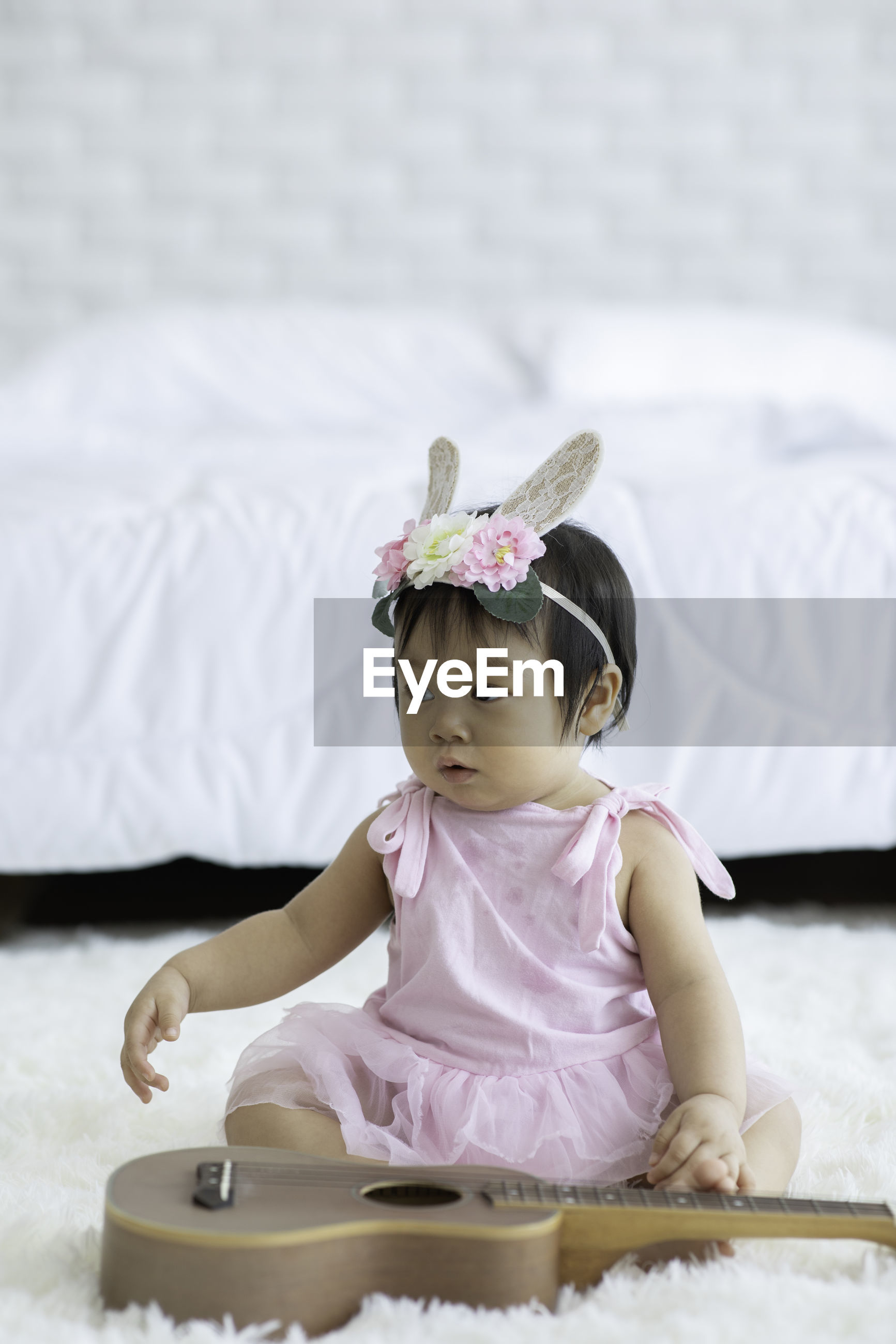 Close-up of cute baby sitting against bed