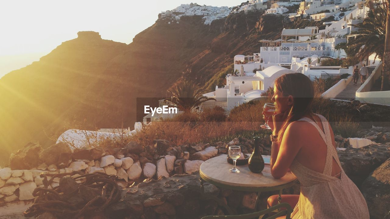 Woman Holding Wineglass While Sitting By Table During Sunset