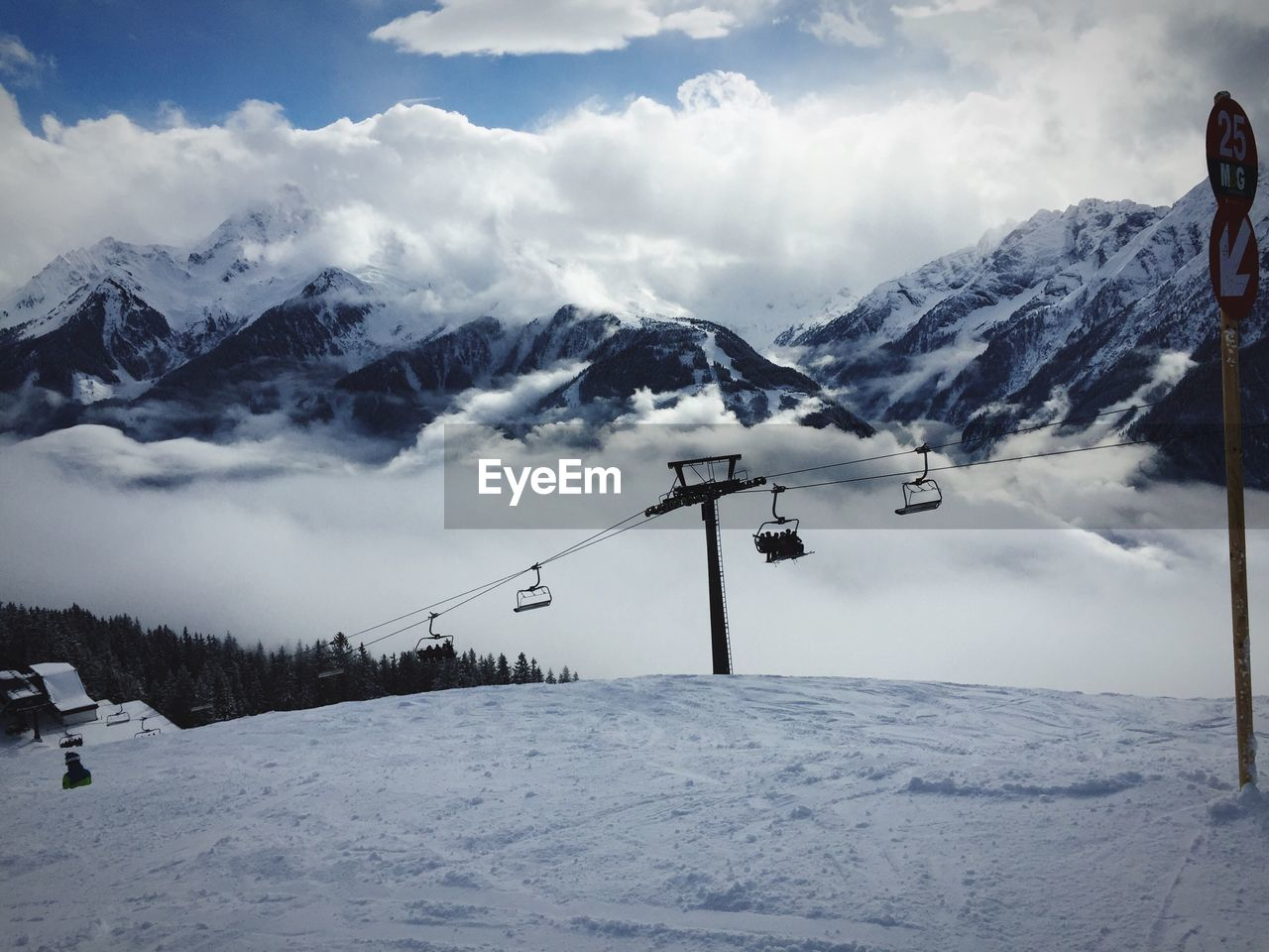 Ski Lift Over Snowy Hill Against Snowcapped Mountains And Cloudy Sky
