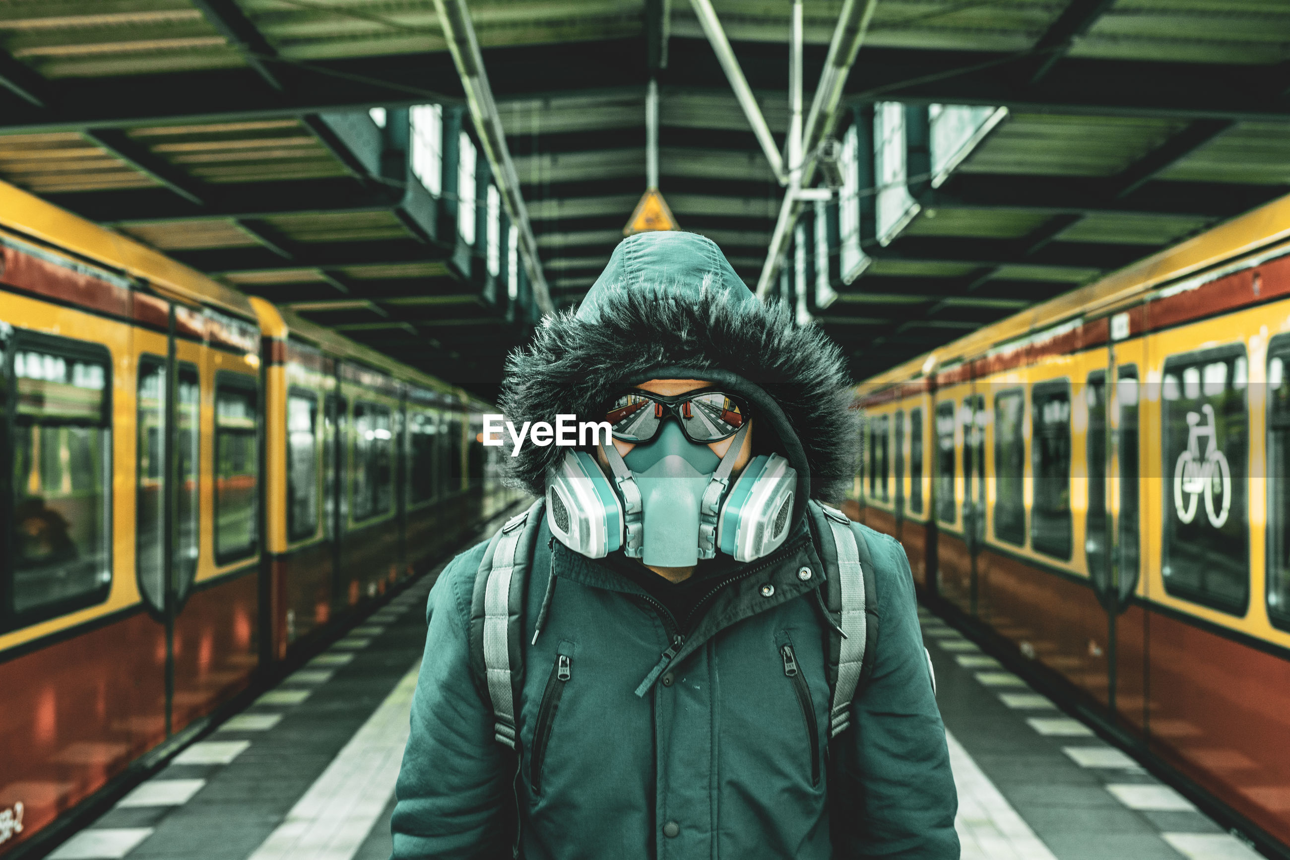 Portrait of man wearing mask standing at railroad station platform