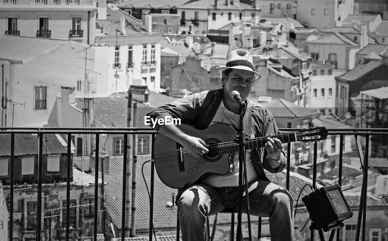 MAN PLAYING GUITAR IN CITY