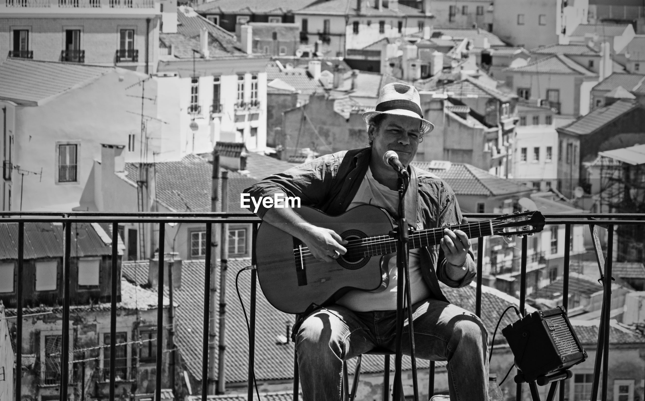 MAN PLAYING GUITAR IN CITY
