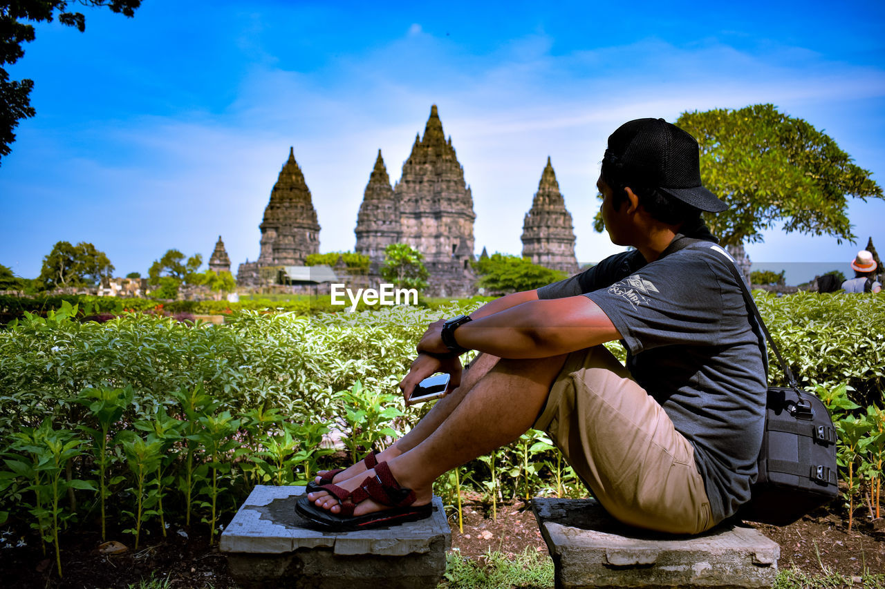 YOUNG WOMAN SITTING ON TEMPLE AGAINST SKY