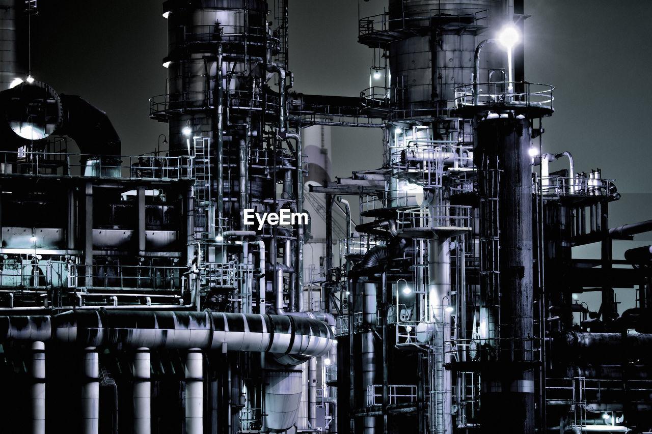 Illuminated Oil Industry Against Sky At Night