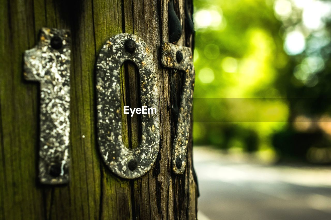 close-up, wood - material, focus on foreground, day, door, metal, outdoors, no people, safety, communication, nameplate