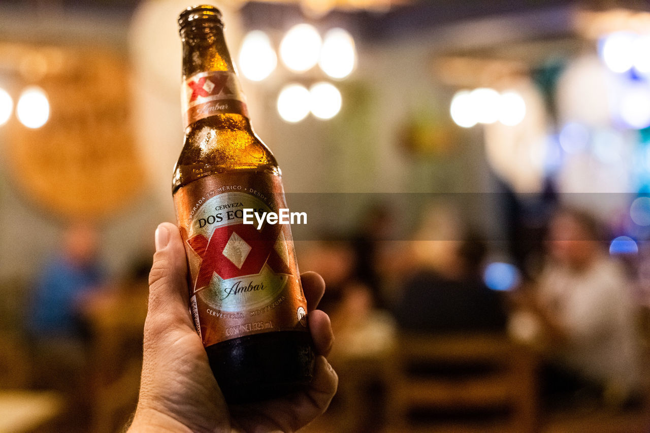 human hand, human body part, focus on foreground, hand, holding, alcohol, refreshment, food and drink, bottle, one person, drink, finger, real people, human finger, close-up, container, indoors, beer - alcohol, body part, beer