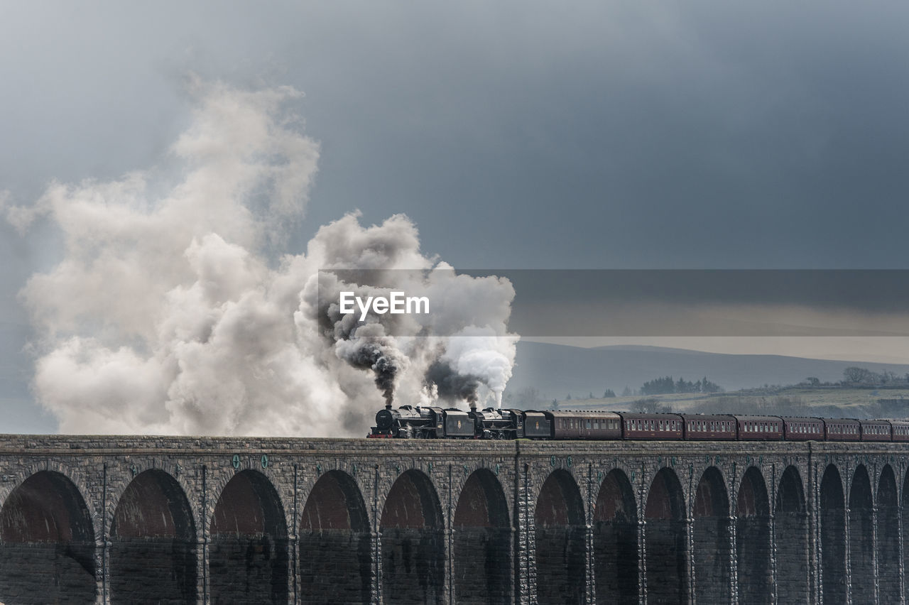 Smoke Emitting From Steam Train On Bridge Against Cloudy Sky