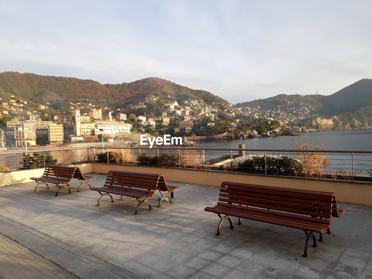 seat, architecture, mountain, bench, built structure, water, building exterior, sky, city, nature, day, building, outdoors, mountain range, sitting, empty, chair, relaxation, river, cityscape, promenade