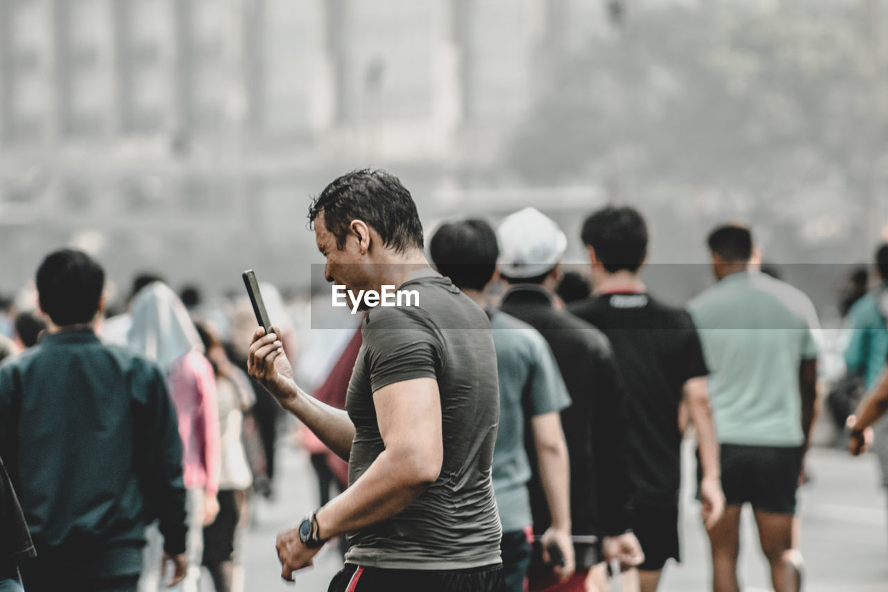 Man using mobile phone while standing in city