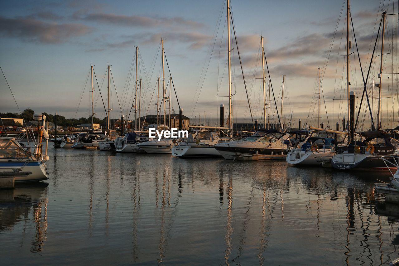 Sailboats Moored In Calm Sea Against Sky