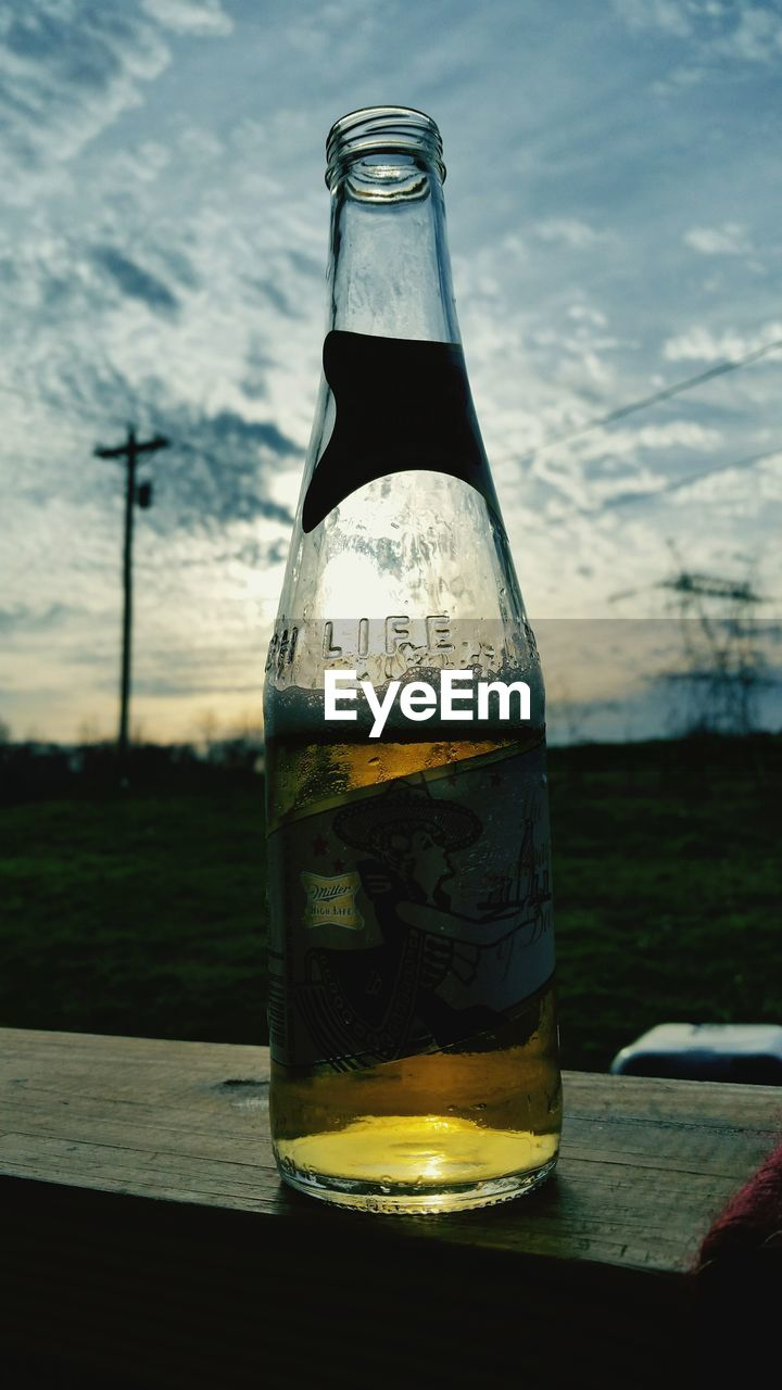 glass - material, drink, drinking glass, bottle, refreshment, table, beer glass, no people, alcohol, food and drink, focus on foreground, beer - alcohol, liquid, freshness, close-up, outdoors, sky, day, water, nature