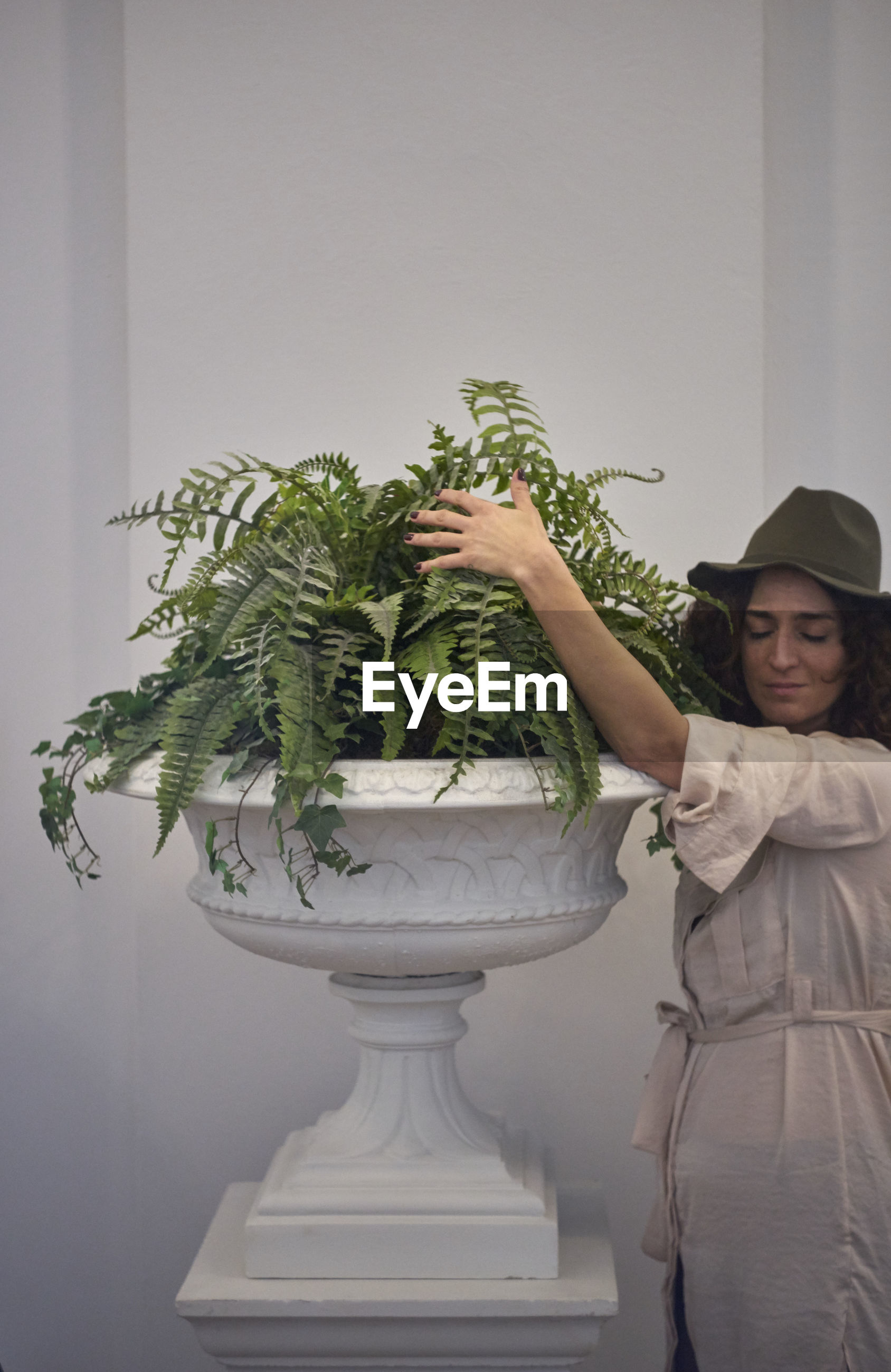 Woman holding plant in urn while standing against wall
