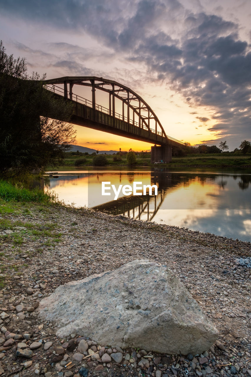 water, sky, bridge, connection, built structure, cloud - sky, bridge - man made structure, architecture, sunset, nature, transportation, river, reflection, no people, rock, solid, rock - object, scenics - nature, stone - object, outdoors, arch bridge