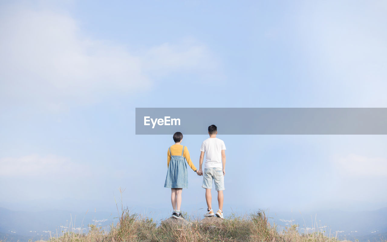 sky, togetherness, rear view, casual clothing, leisure activity, men, two people, real people, lifestyles, bonding, full length, women, day, standing, love, nature, couple - relationship, people, beauty in nature, cloud - sky, positive emotion, outdoors, arm around, looking at view, shorts