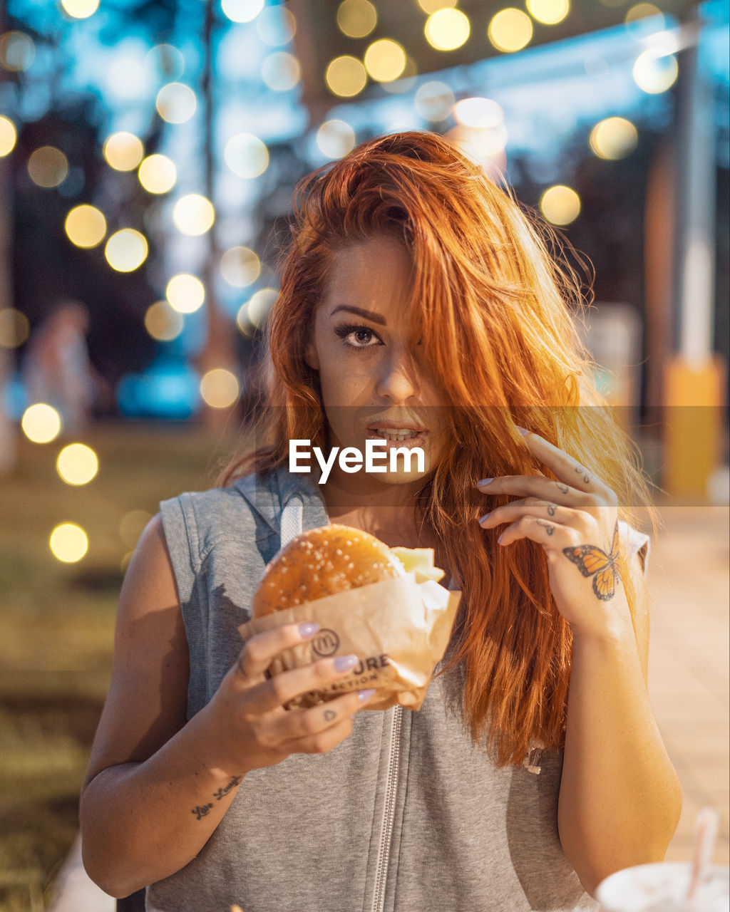 Portrait Of Woman Holding Burger In City At Night
