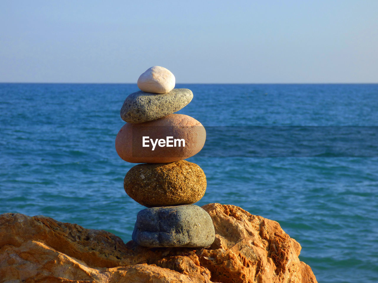 Stack Of Stones On Rock By Sea Against Clear Sky