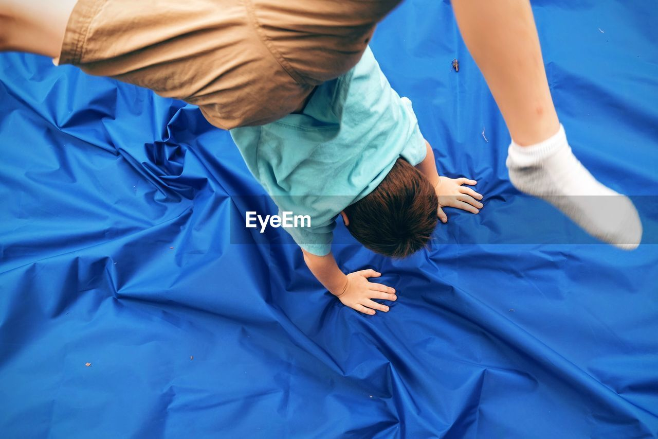 High angle view of boy performing handstand on blue fabric in yard