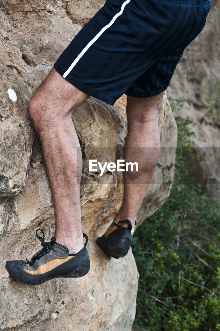 Low Section Of Man Climbing On Mountain